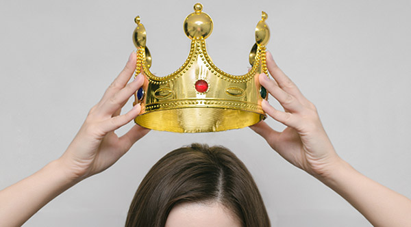Woman girl holding above a head the golden crown.